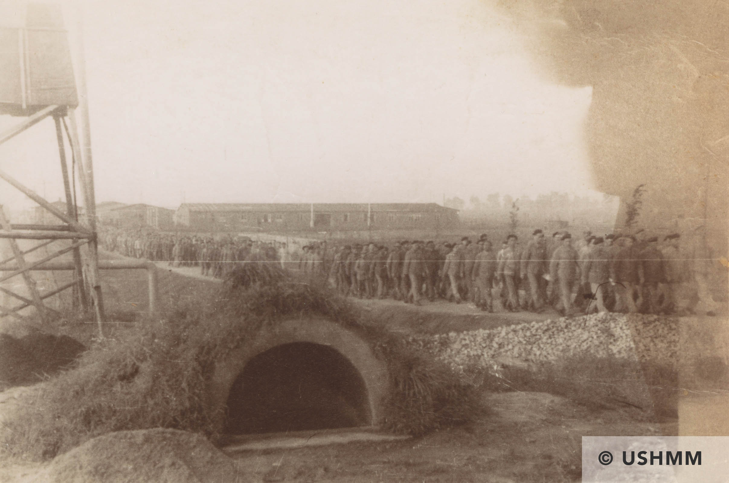 A column of prisoners walks from the Buna camp towards the I.G. Farben works. USHMM 57718