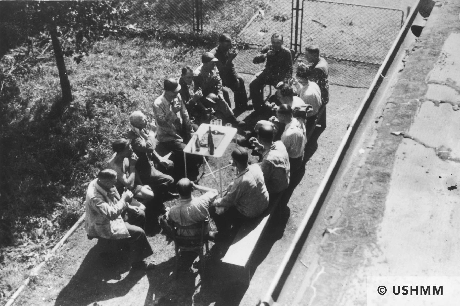 Auschwitz personnel, including many physicians, enjoy drinks at an outdoor table drinking following a visit to a coal mine. 1944 USHMM 34795