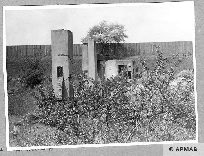Foreground two concrete columns of main gate background concrete bunker most probably fragment of guard tower 1962 APMAB 926