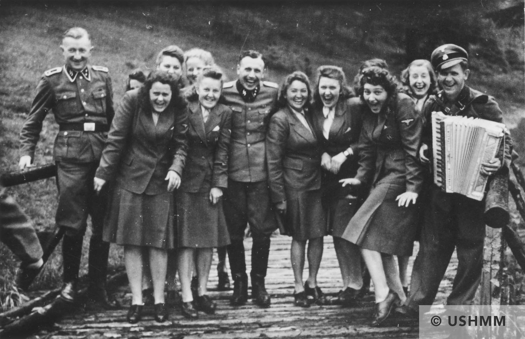 Nazi officers and Helferinnen pose on a wooden bridge in Solahütte. USHMM 34585