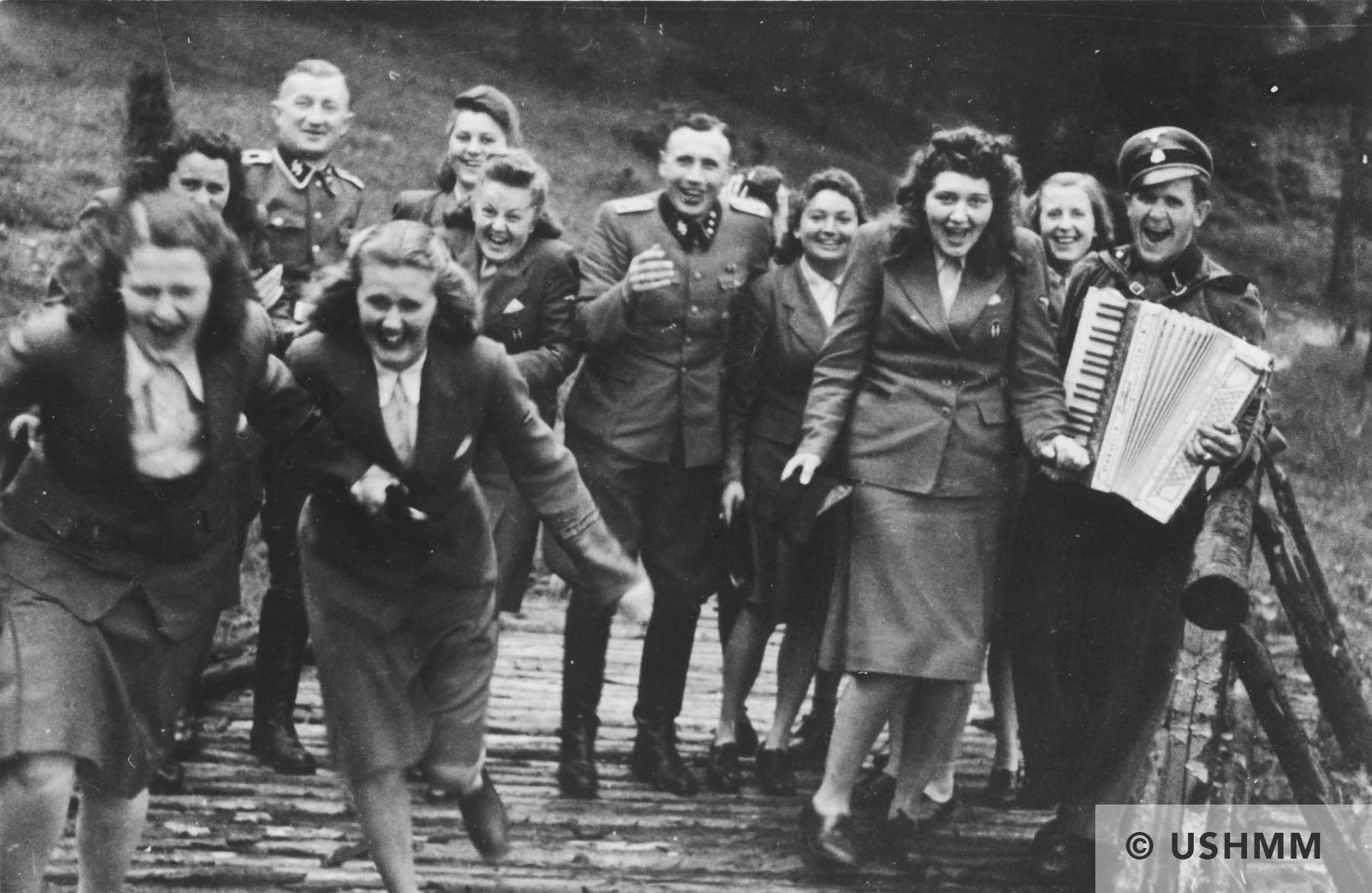 Nazi officers and female auxiliaries (Helferinnen) run down a wooden bridge in Solahütte. USHMM 34586