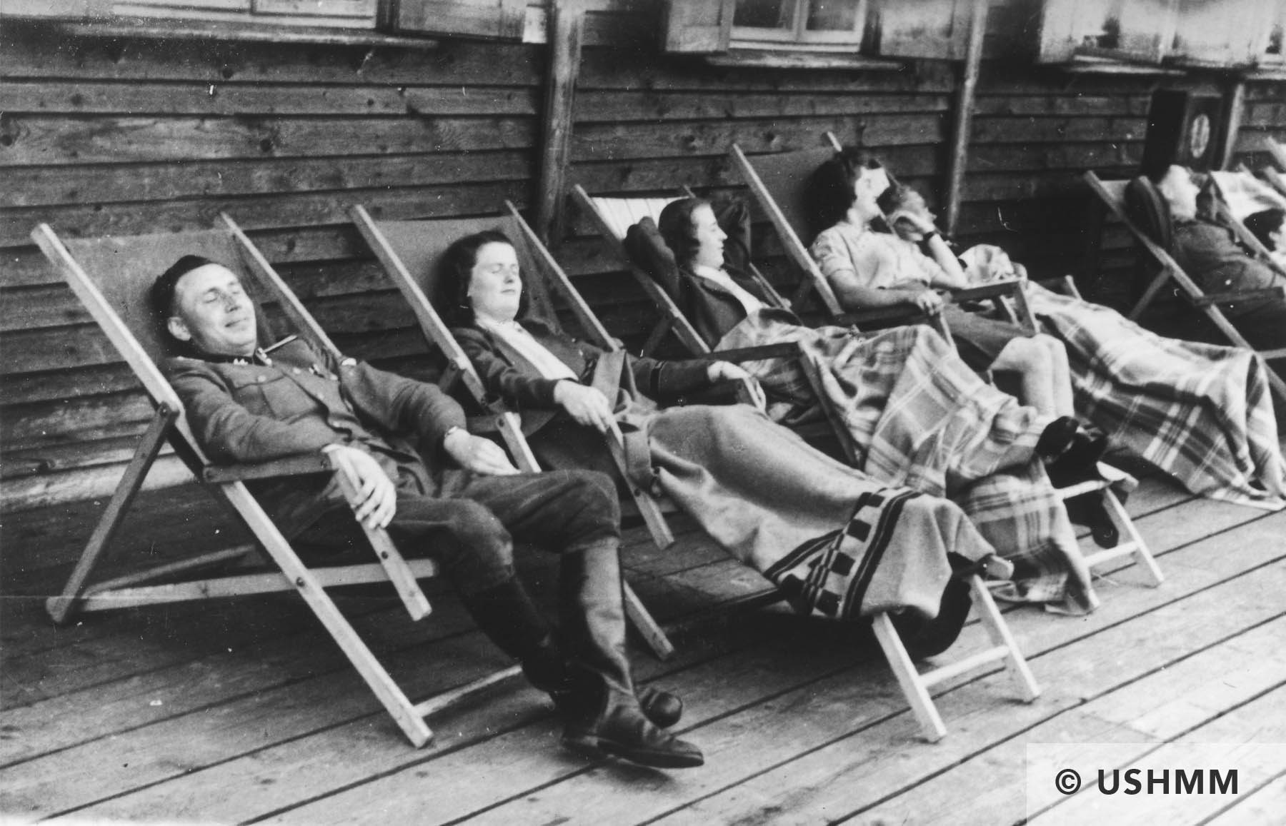 SS Officer Karl Höcker and some women relax on lounge chairs on a deck in Solahütte. USHMM 34584