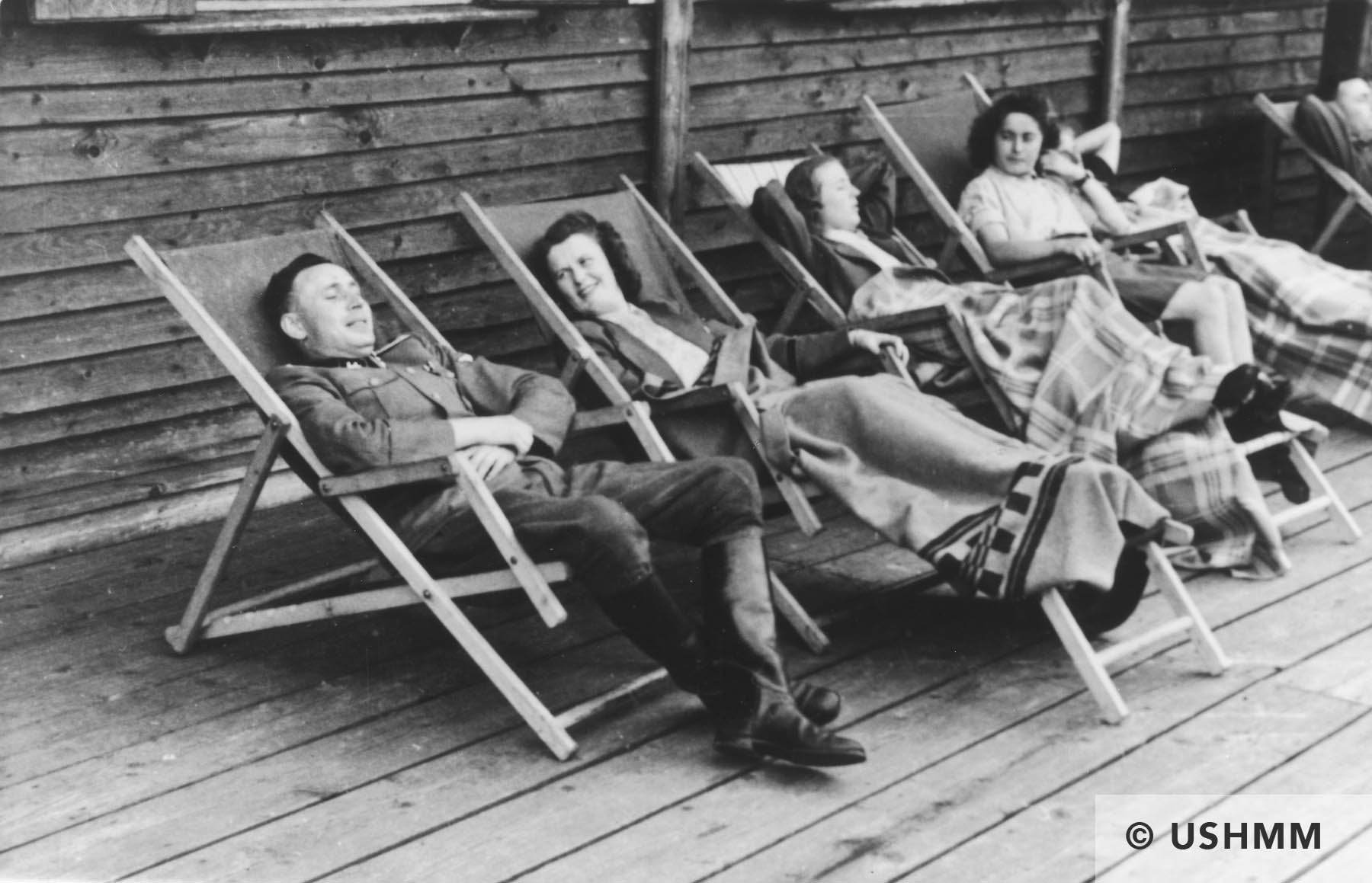 SS officer Karl Höcker relaxes with women in lounge chairs on the deck of the retreat in Solahütte. USHMM 34582