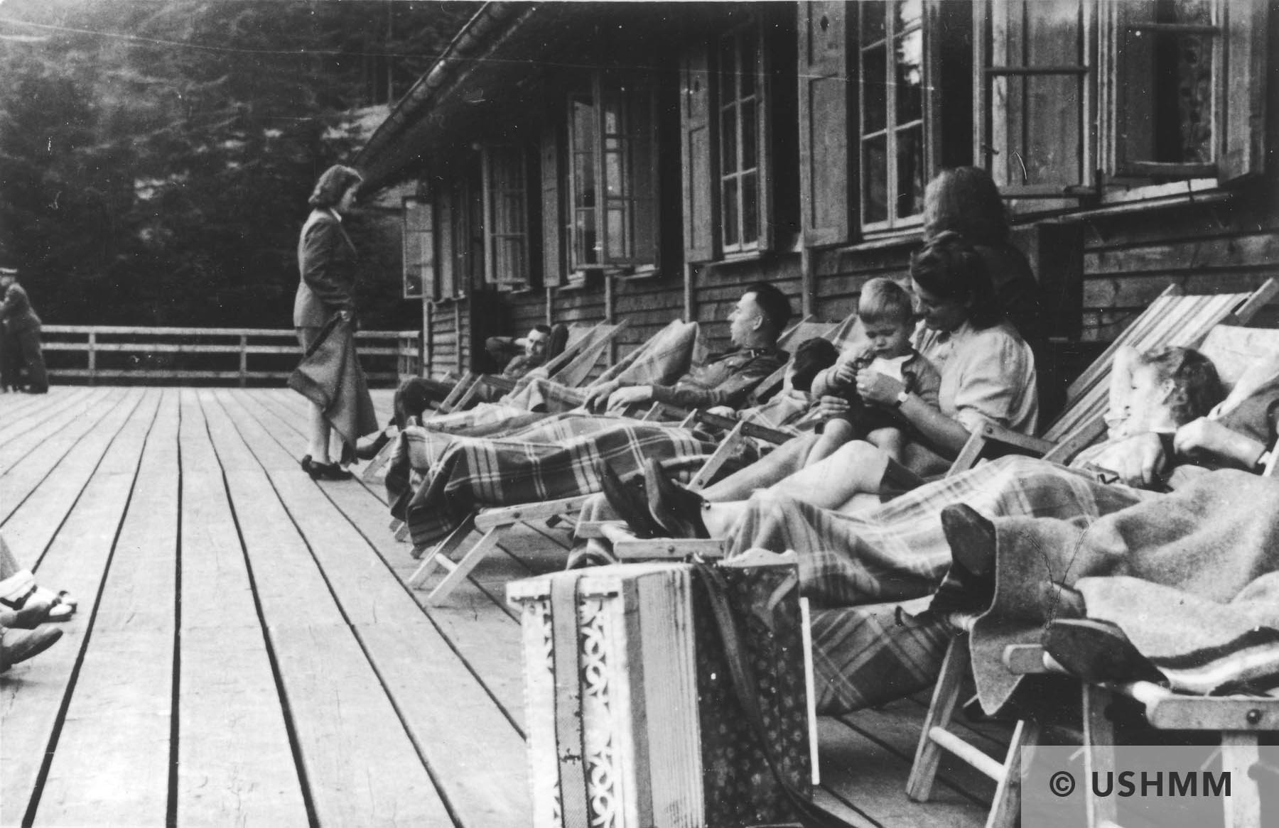 SS officers together with women and a baby relax on lounge chairs on a deck in Solahütte. USHMM 34583