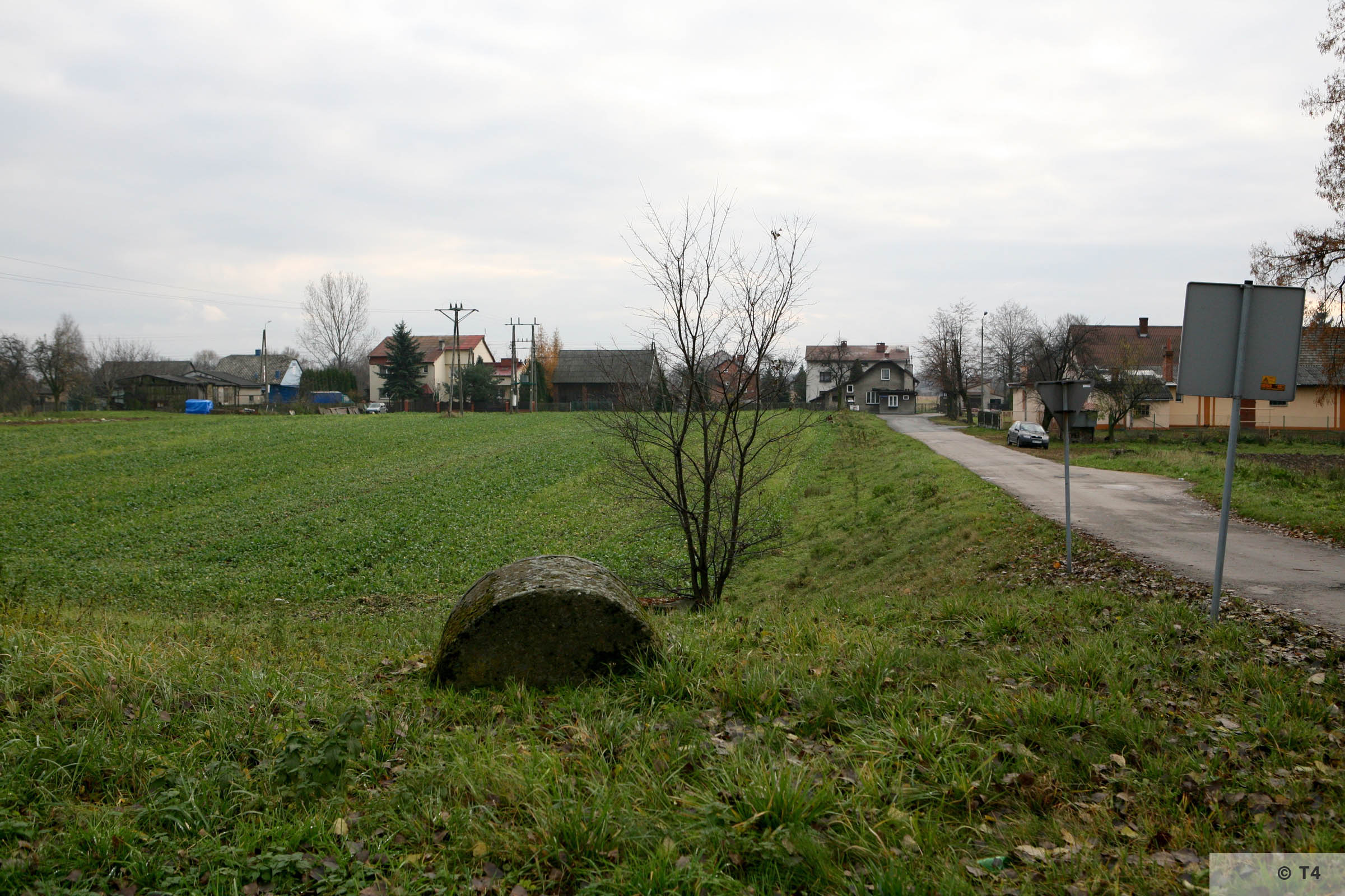 View towards the main entrance gate of the former camp and Blockführerstube. Area of Erziehungslager on the left. SS barrack on the right. 2008 T4 3353